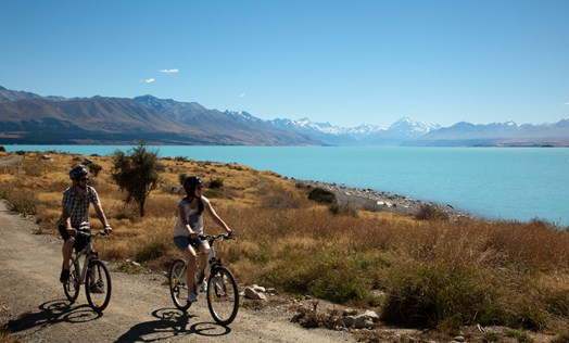 Cyclist riding Alps 2 Ocean trail beside Lake Pukaki with Mt Cook in the background